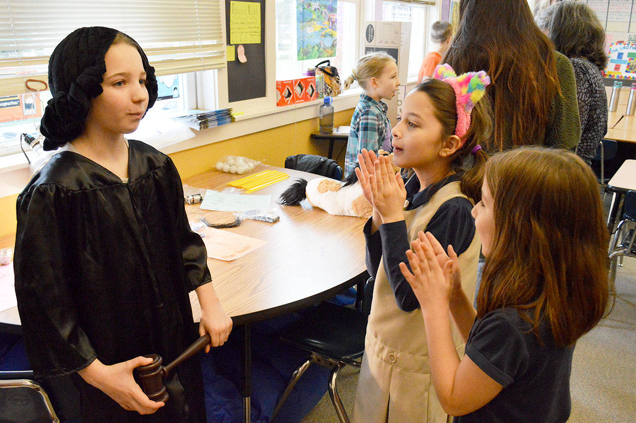 Allison Garcia (front right) and Angelina Heroff applaud after Emilie Perrin's presentation on Sonia Sotomayor on Wednesday. Perrin was one of around 70 fourth graders who either dressed up as their chosen notable person or created a poster. Photo by Laura Guido/Whidbey News-Times